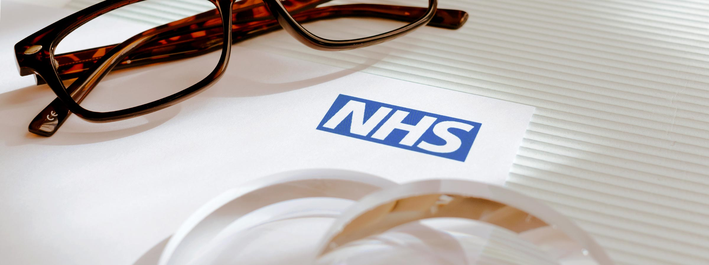 Glasses frames and lenses lying on a piece of paper with the NHS logo