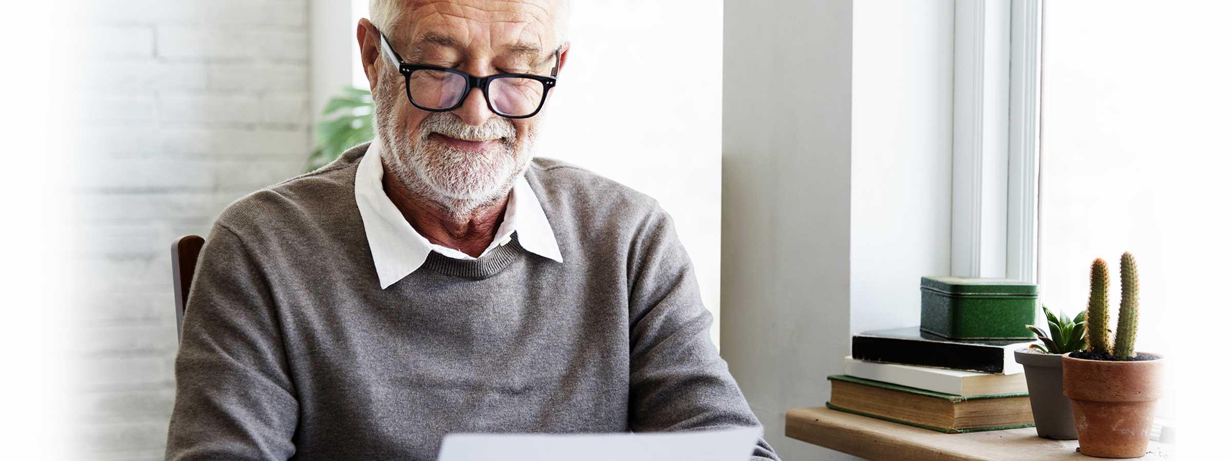 An older man reading through glasses
