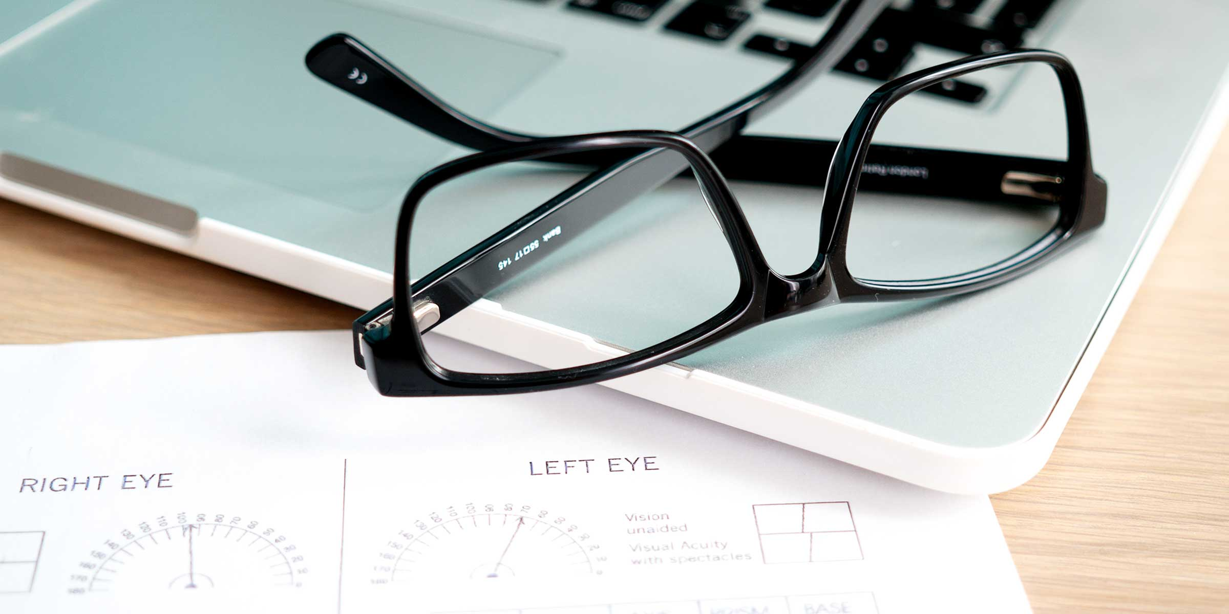 A black glasses frame lying on a laptop
