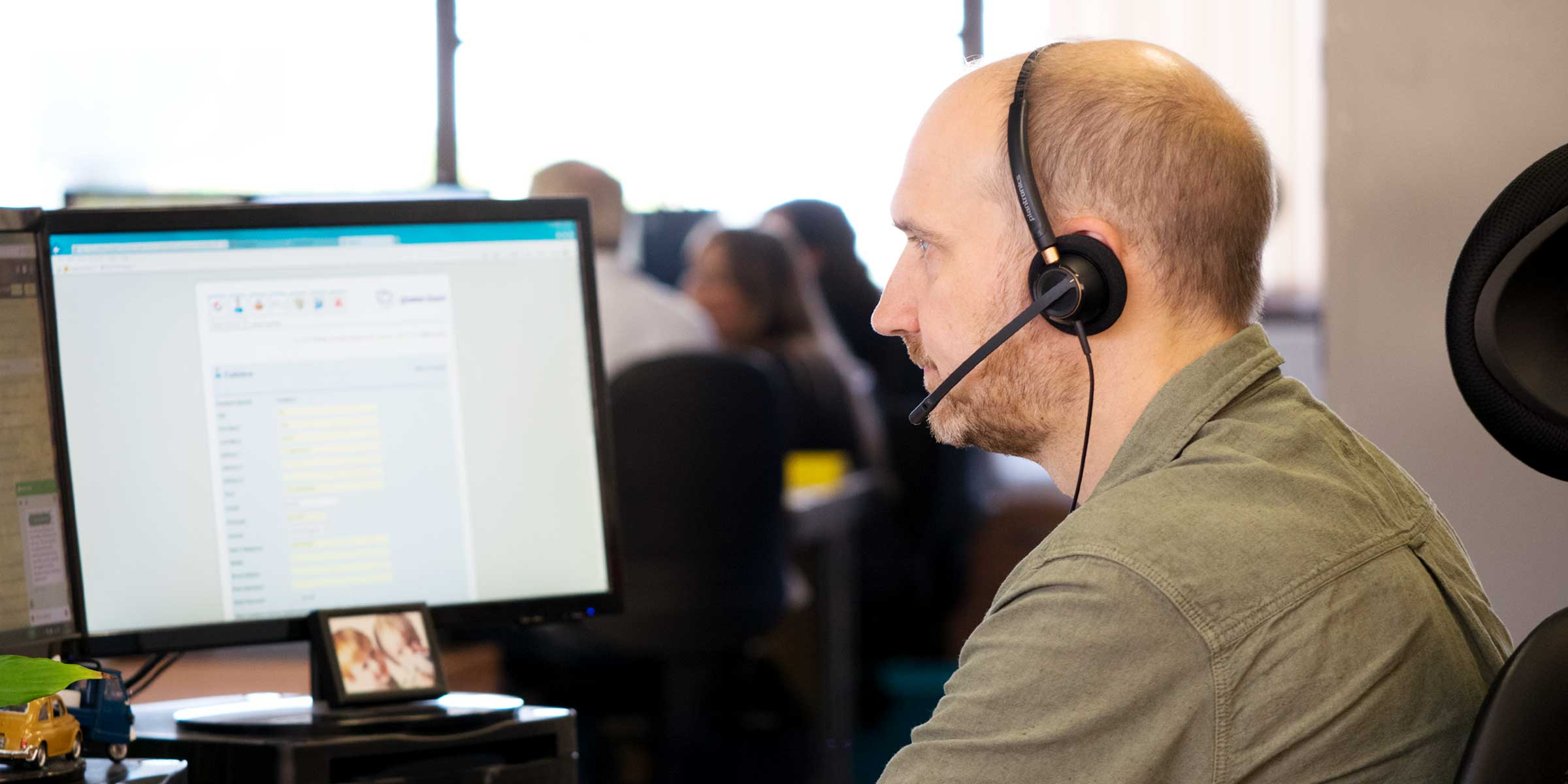 A customer service agent with a headset on and at his computer