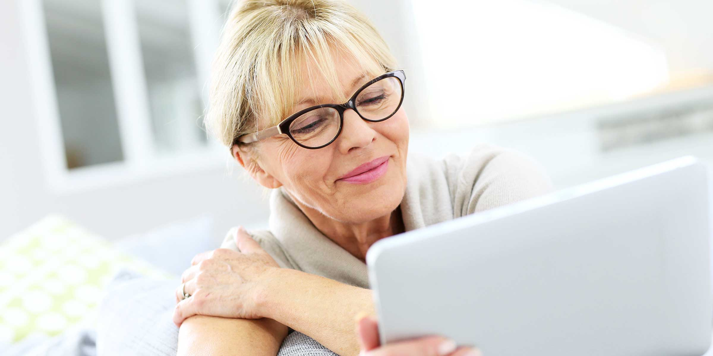 Older woman with glasses looking at a tablet
