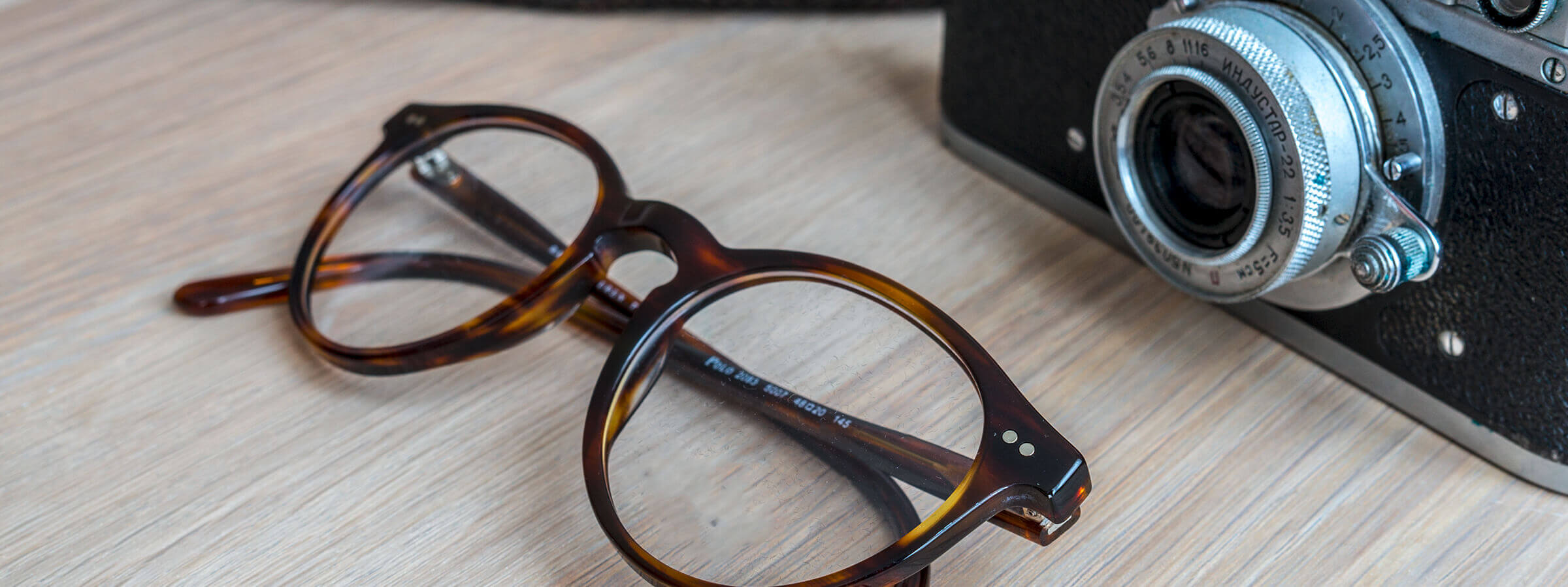 A pair of glasses lying next to a camera