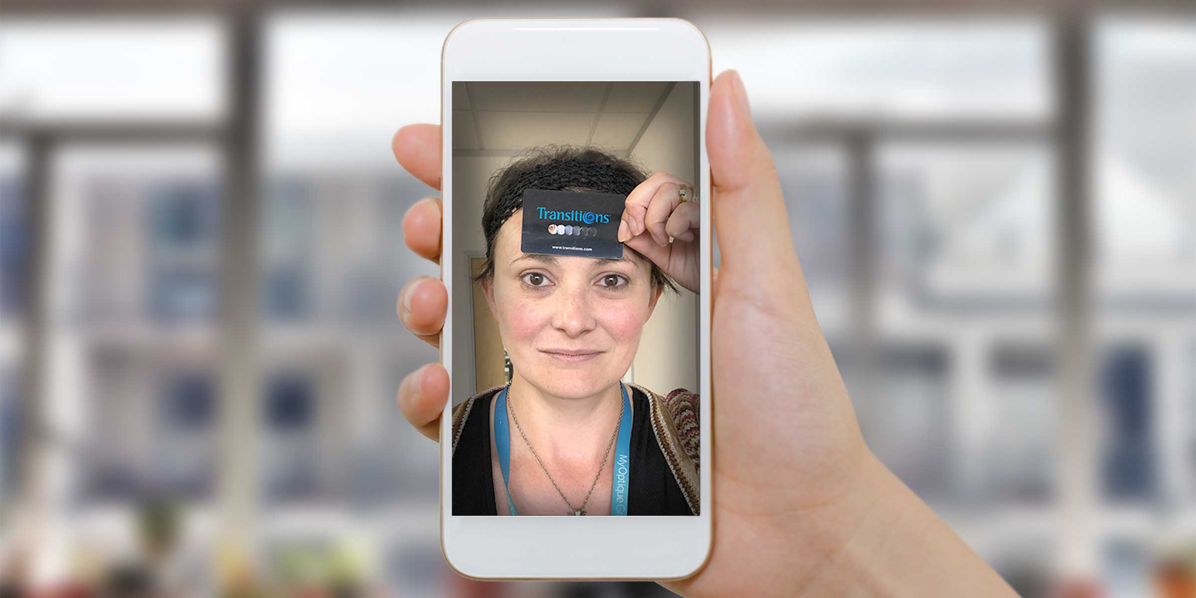 A woman taking a selfie with a card on her forehead
