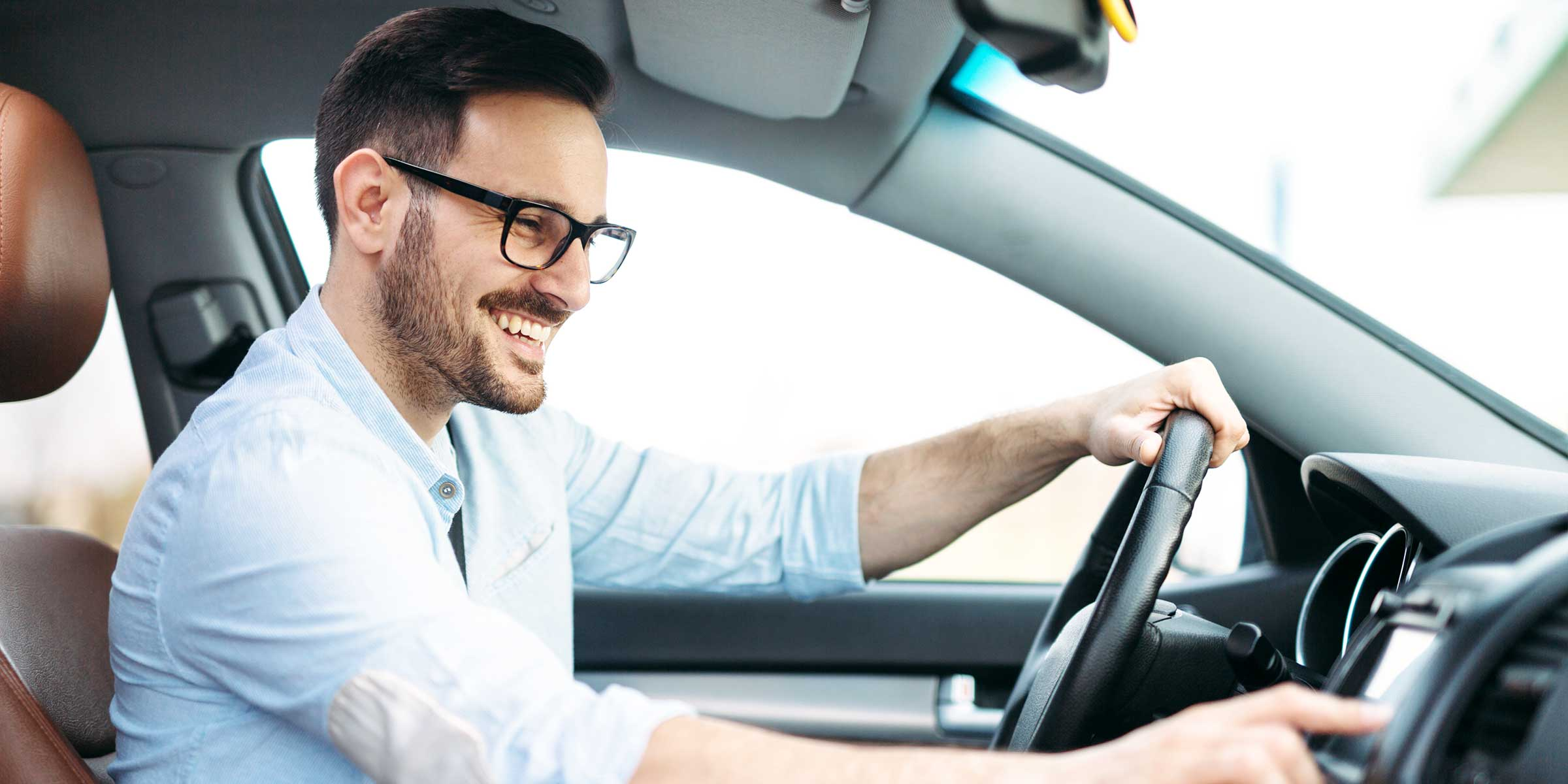 A smiling man with glasses driving a car