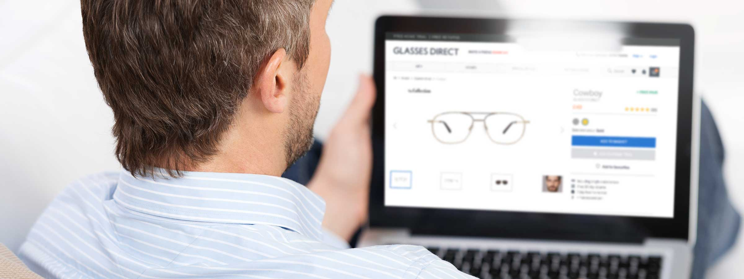 Man looking at the Glasses Direct website on a laptop