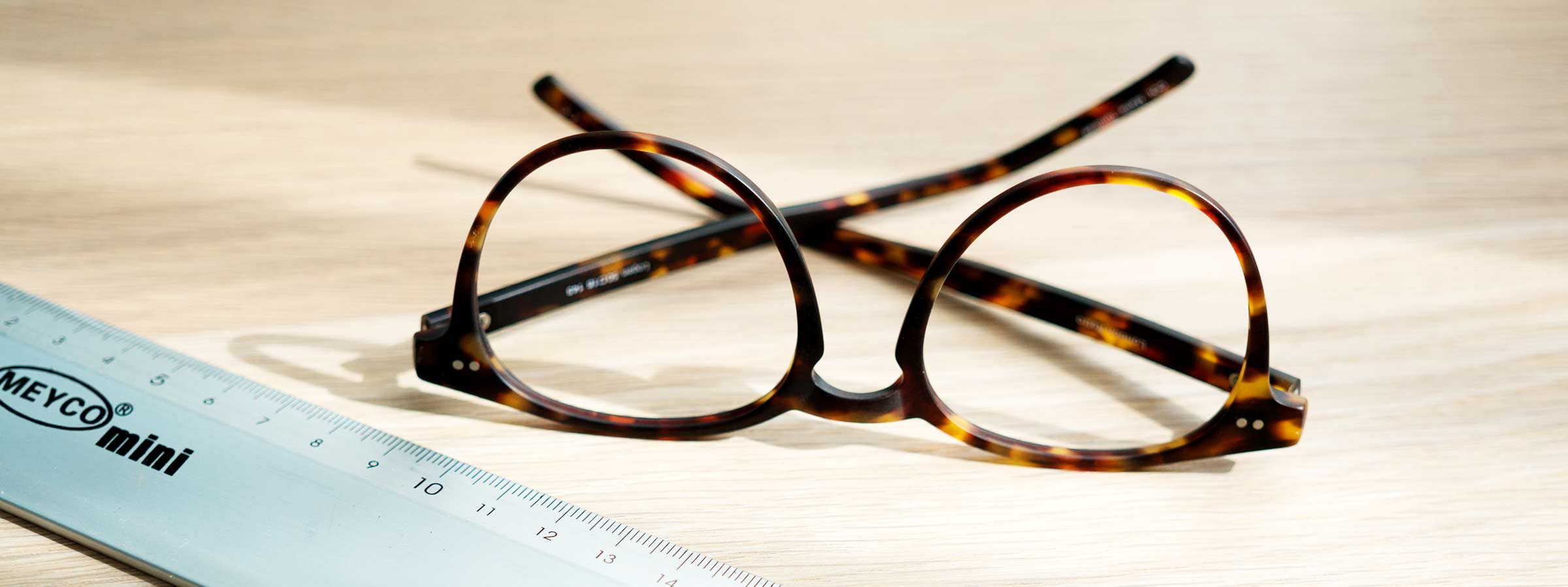 A pair of glasses next to a ruler
