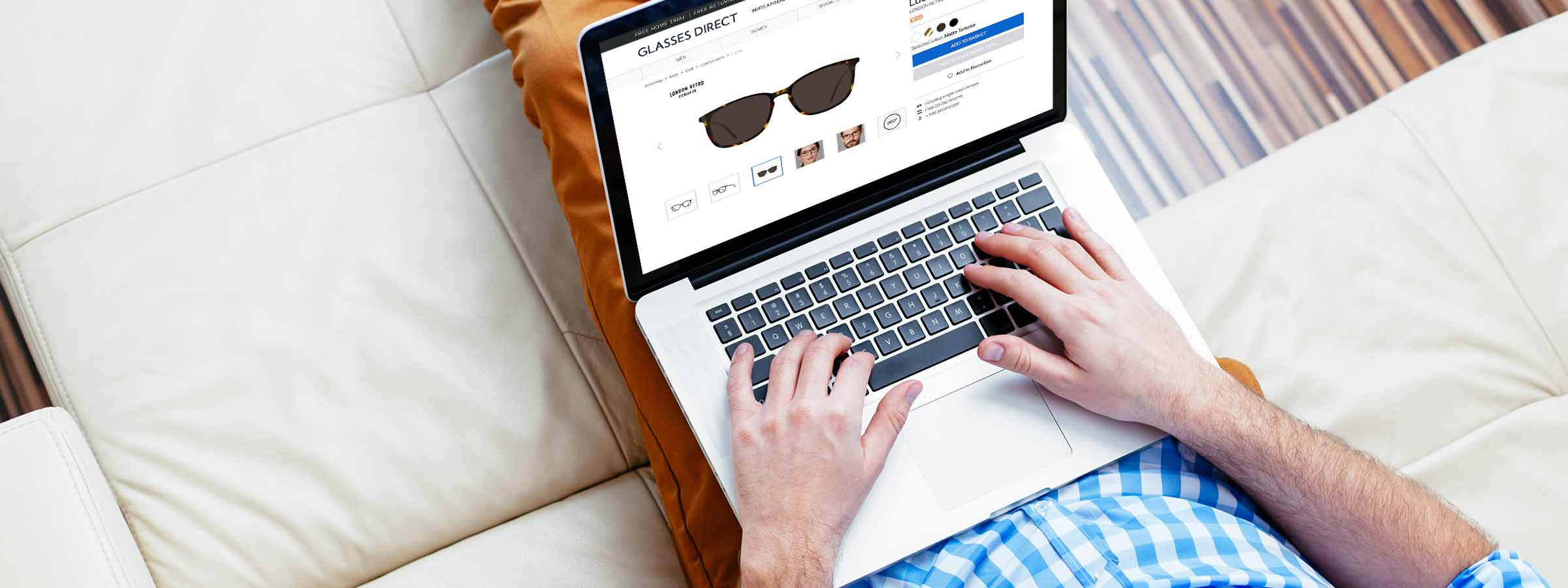 A man looking at a pair of prescription sunglasses on Glasses Direct on his laptop