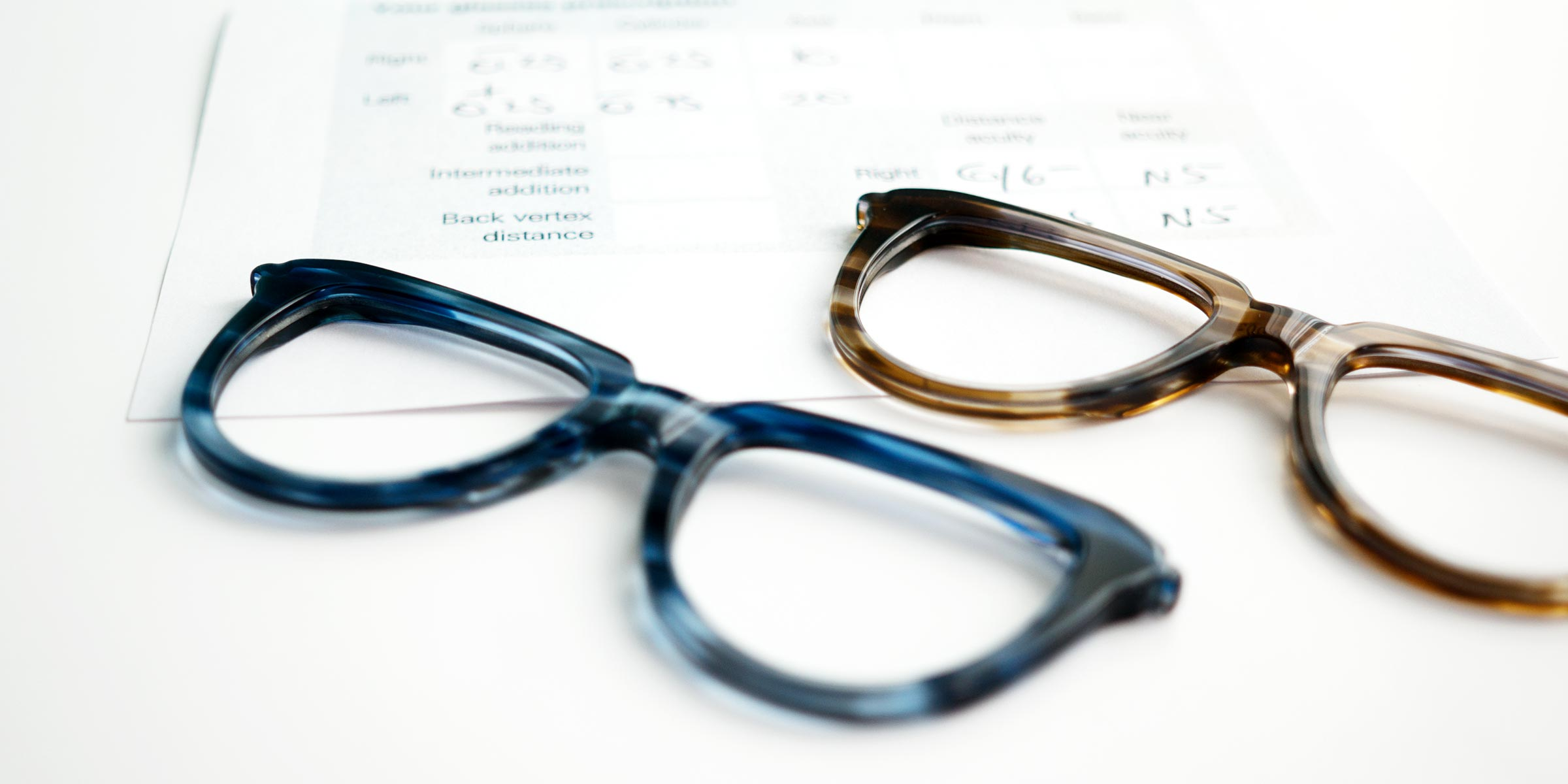 Glasses frames lying next to a prescription form