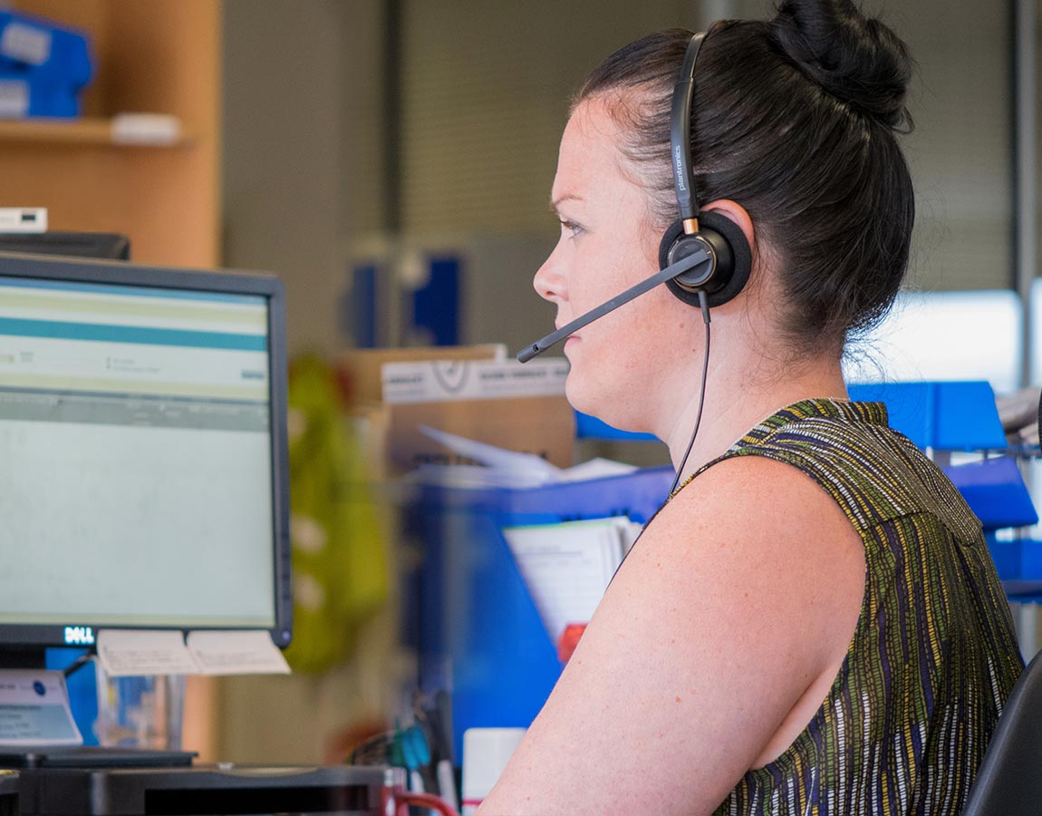 A customer service agent with a headset looking at a computer screen