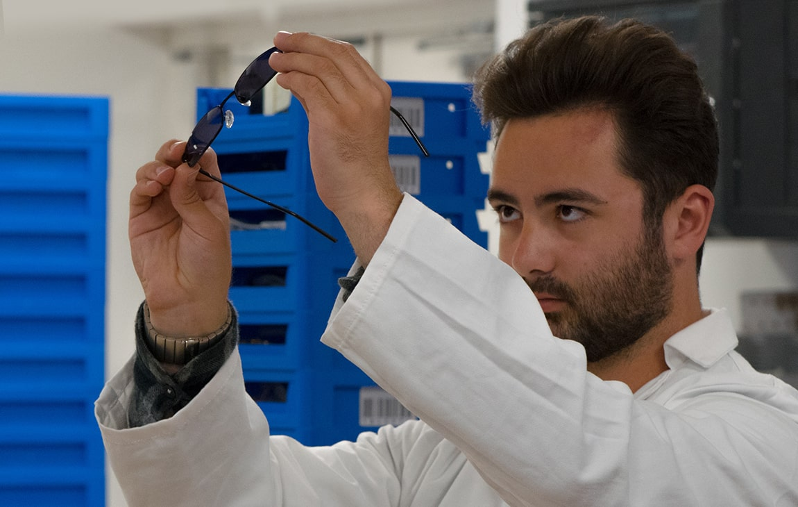 A lab technician inspects a pair of sunglasses