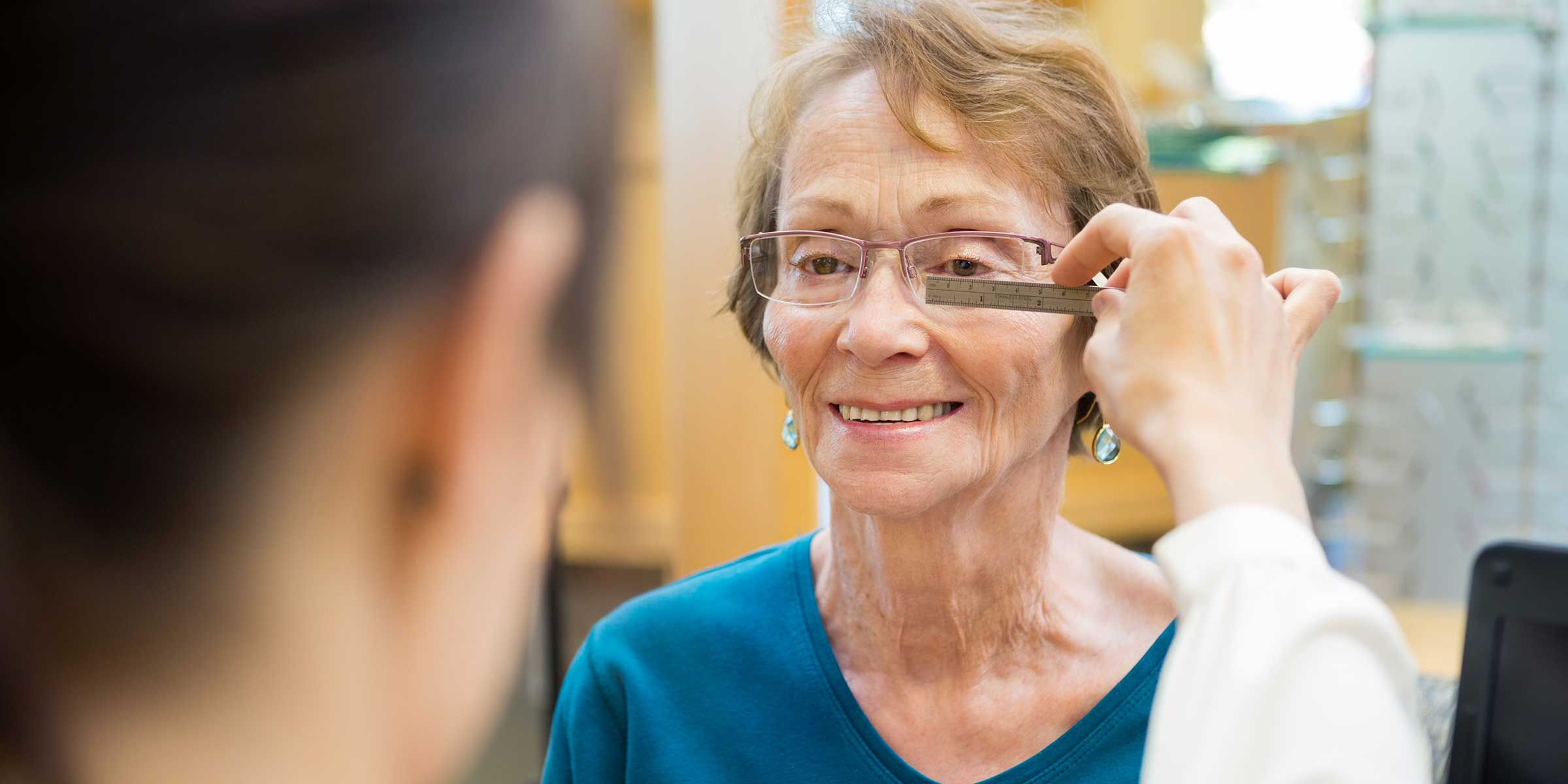 An optician measuring a woman's PD