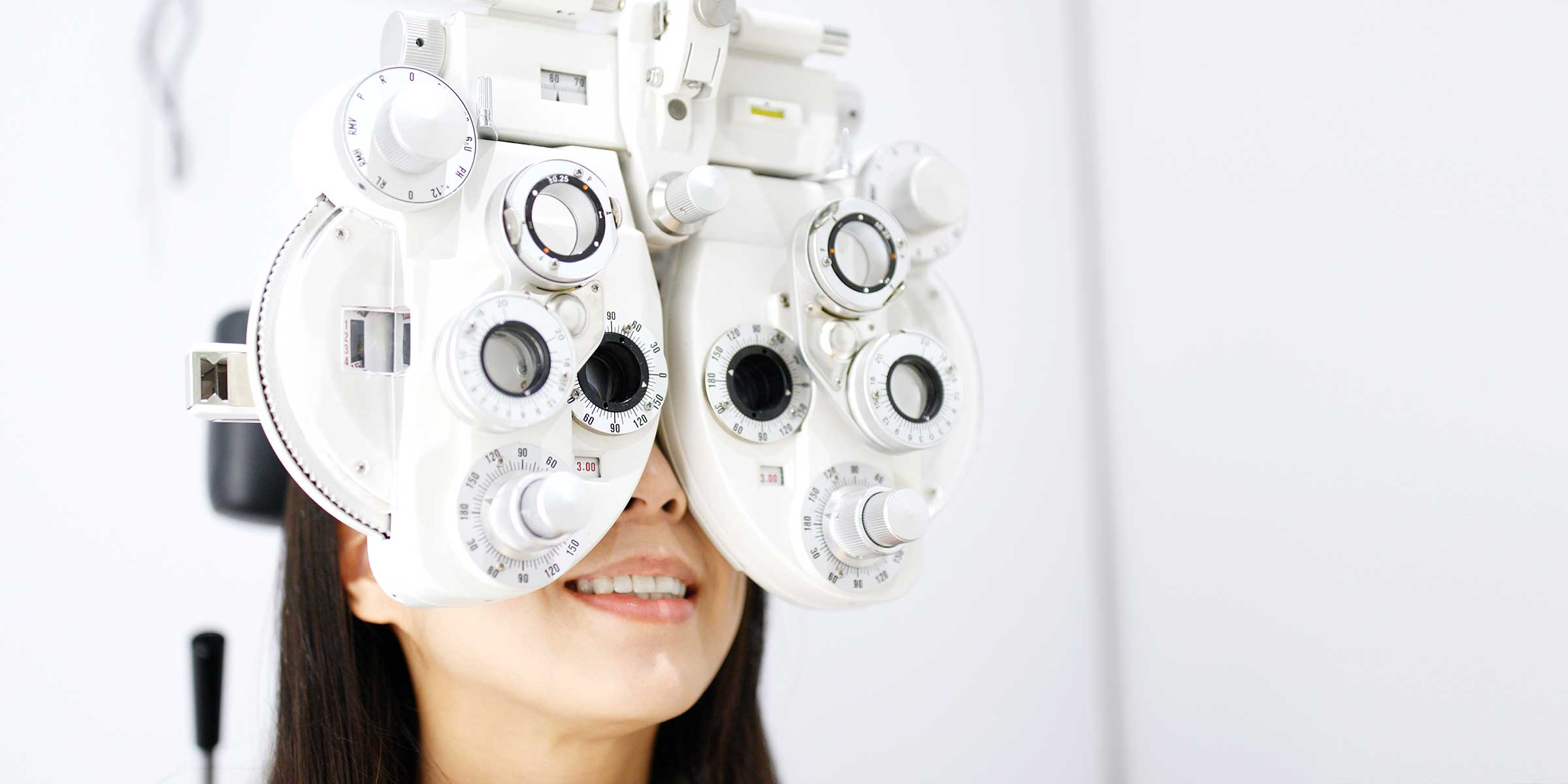 A woman looking through a phoropter during an eye examination