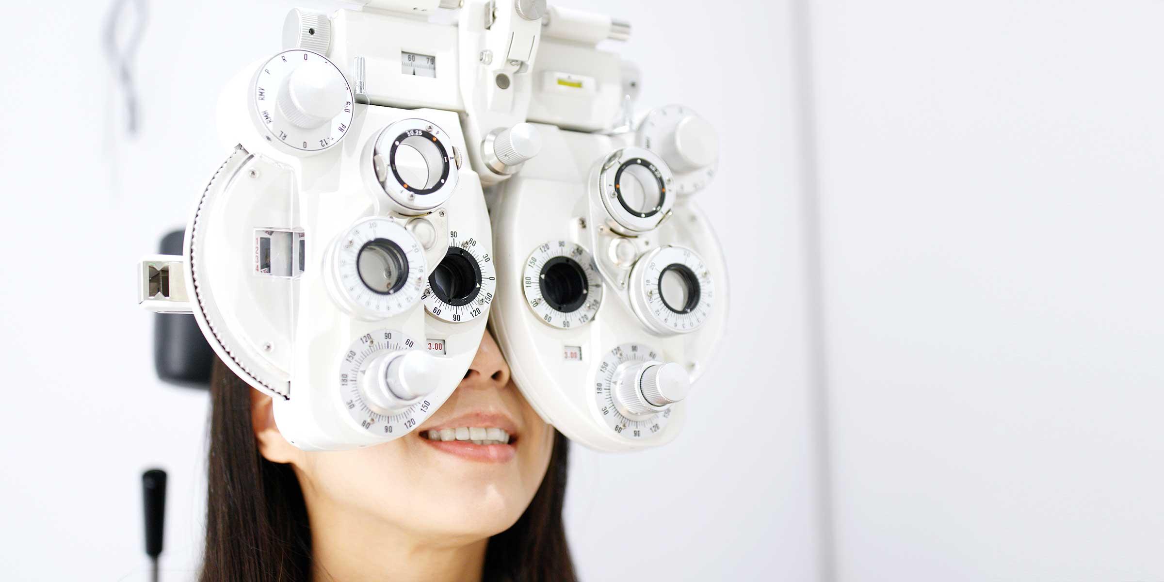 A woman looking through a phoropter during an eye examination