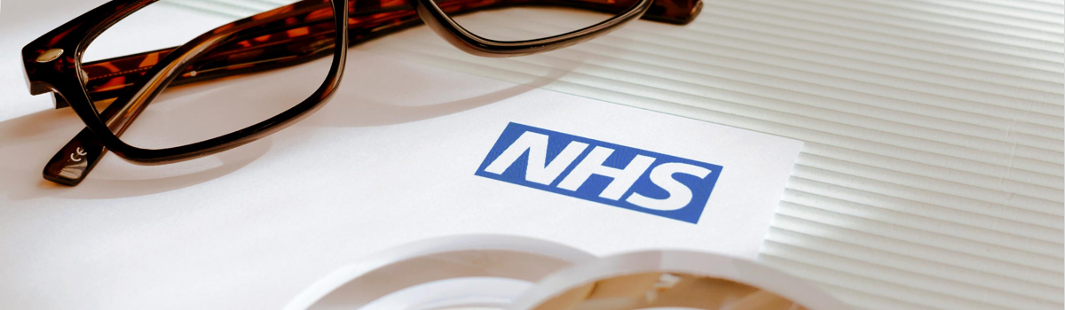 Glasses frames lying next to an NHS letterhead